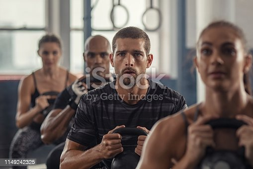 Portrait of fitness man lifting kettle bell with young women in fitness center. Active guy with group of people in gym doing weight lifting with kettlebell. Determined people in a row squatting in gym gym.