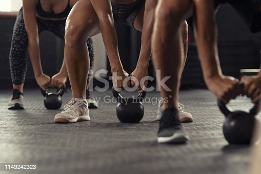 Closeup of young man and fit woman hands lifting kettle bell while squatting at gym. Athlete people in fitness center doing weight lifting with kettlebell. Group of three young athlete doing cross training training.