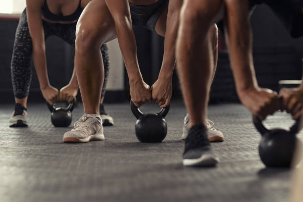 Fitness people hands lifting kettle bell Closeup of young man and fit woman hands lifting kettle bell while squatting at gym. Athlete people in fitness center doing weight lifting with kettlebell. Group of three young athlete doing cross training training. health club stock pictures, royalty-free photos & images