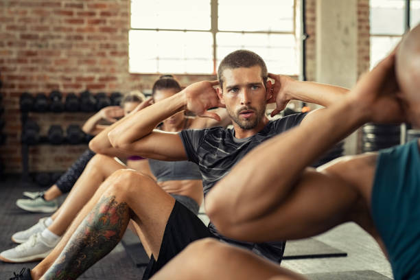 Fitness people in a row doing sit ups Determined young man doing exercise for abdominal. Athletic class doing abs in a row. Fitness man in gym exercising while sitting on mat in fitness center during cardio course. exercise class stock pictures, royalty-free photos & images