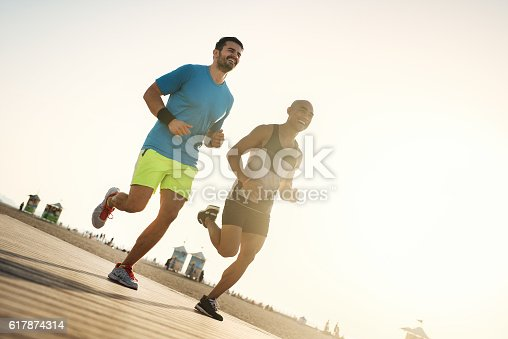 istock Fitness people running at the beach into the sunset. 617874314