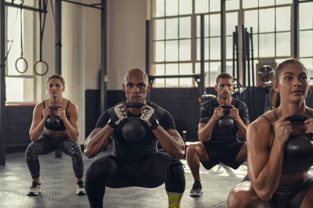 fitness people squatting with kettlebell - class стоковые фото и изображения