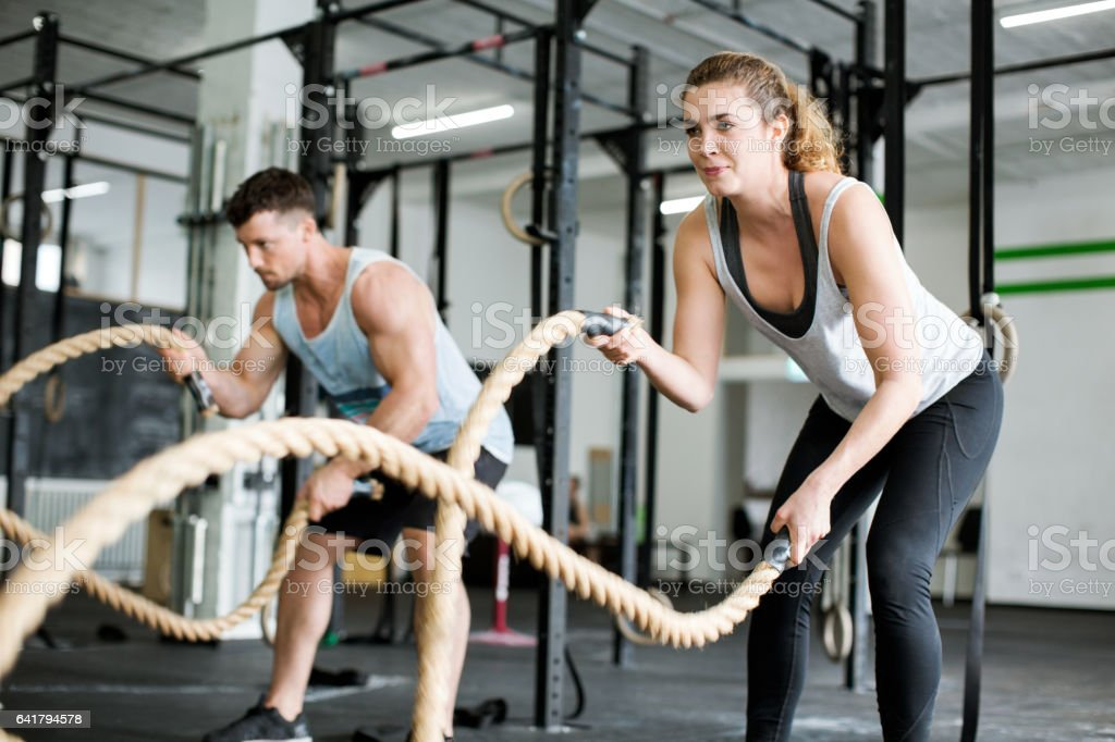 Fitness people working out with battle ropes stock photo