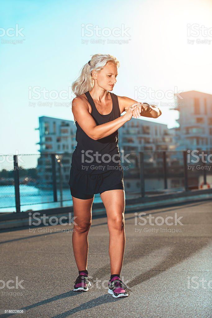 Fitness practice outside with female runner wearing smart watch stock photo