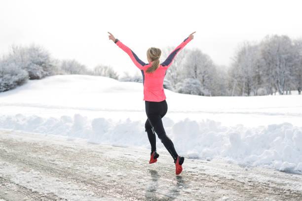 fitness laufen frau in der wintersaison - joggerin stock-fotos und bilder