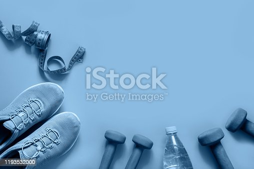 Fitness set with dumbbells,measuring tape, fitness shoes,bottle of water on blue background. View from above, space for your text. Trendy color Classic blue of the 2020 year.