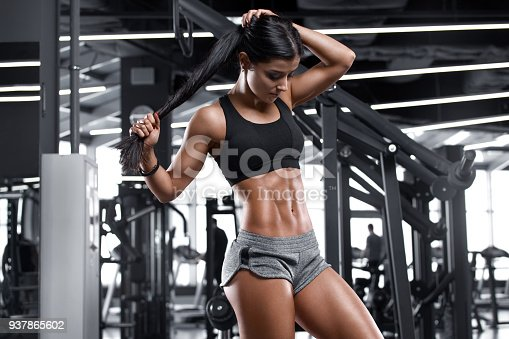 istock Fitness sexy woman showing abs and flat belly. Beautiful muscular girl, shaped abdominal 937865602
