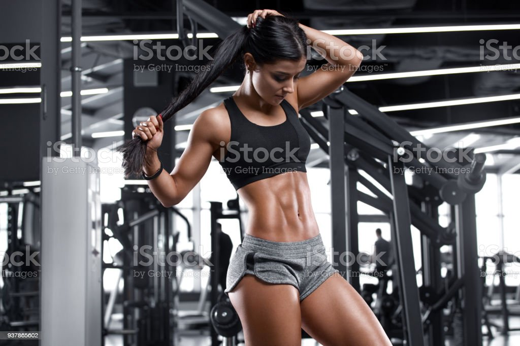 Fitness sexy woman showing abs and flat belly. Beautiful muscular girl, shaped abdominal stock photo