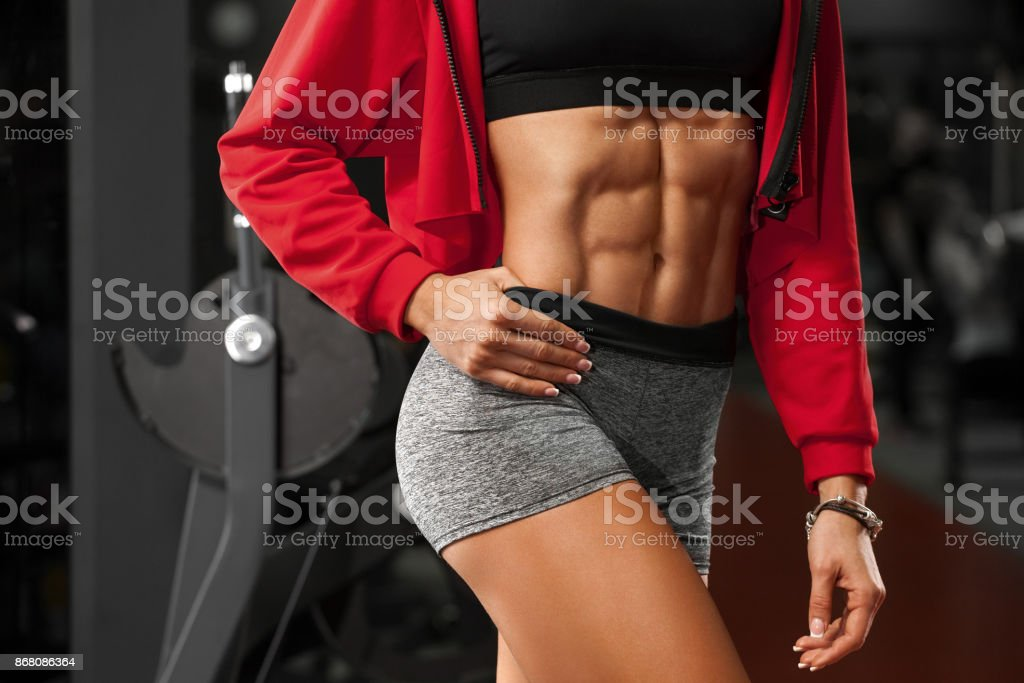 Fitness sexy woman showing abs and flat belly in gym. Beautiful athletic girl, shaped abdominal, slim waist Fitness sexy woman showing abs and flat belly in gym. Beautiful athletic girl, shaped abdominal, slim waist Abdomen Stock Photo