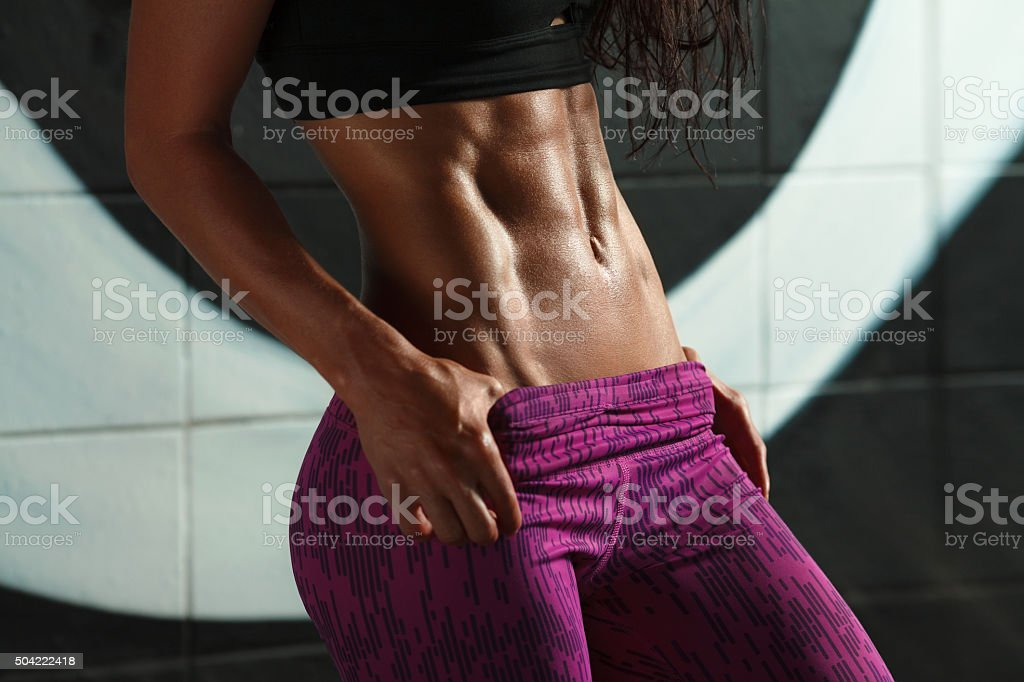 Fitness sexy woman showing abs and flat belly, slim waist stock photo