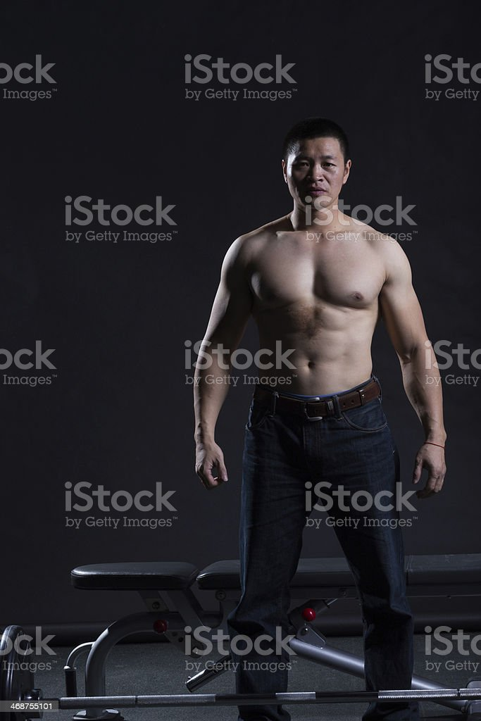 fitness shaped muscle man posing on dark gym stock photo