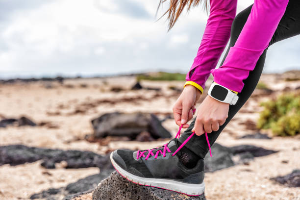 Fitness smartwatch woman runner getting run ready Fitness smartwatch woman runner lacing running shoes on beach, Athlete girl getting ready for run workout tying running shoe laces outside wearing watch gear. Healthy lifestyle concept. fitness tracker stock pictures, royalty-free photos & images