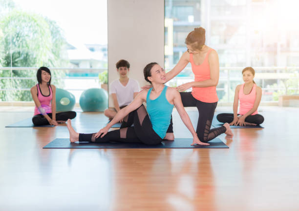 fitness, sport, training, gym and lifestyle concept - group of smiling women with trainer stretching on mats in the gym stock photo