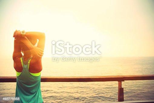 istock fitness sports woman stretching  on wooden boardwalk seaside 493275568
