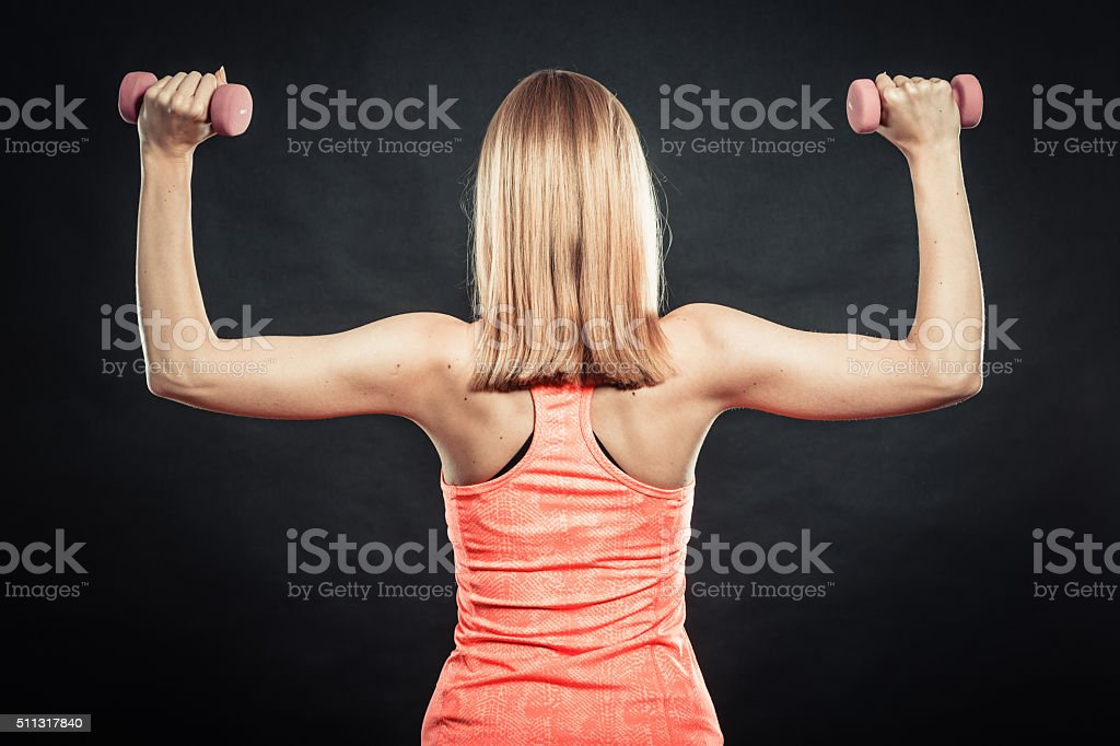 Fitness sporty girl lifting weights back view stock photo