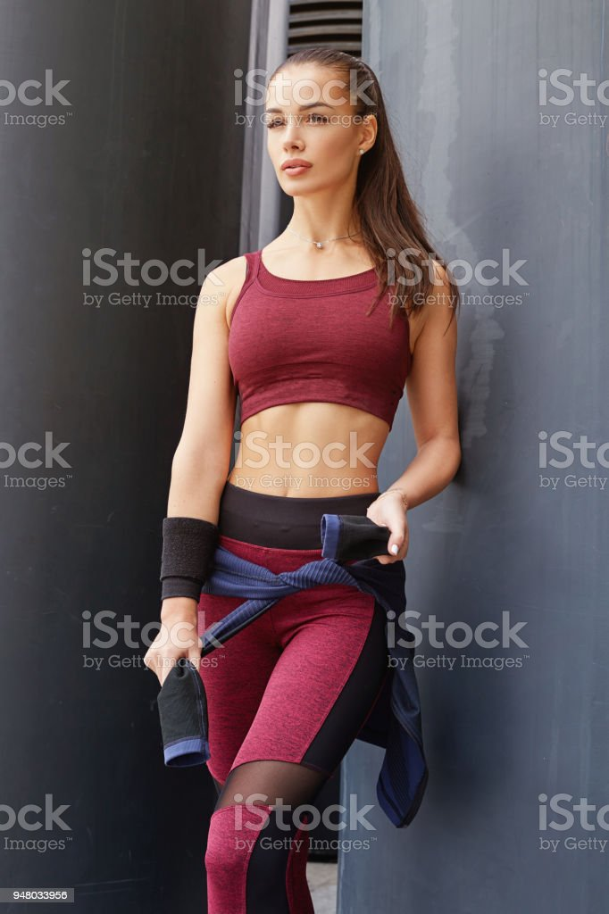 06f9b20211 Fitness sporty woman with headphones during outdoor exercises workout.  Beautiful fit Girl in sport wear. Fitness model outdoors. Weight Loss.