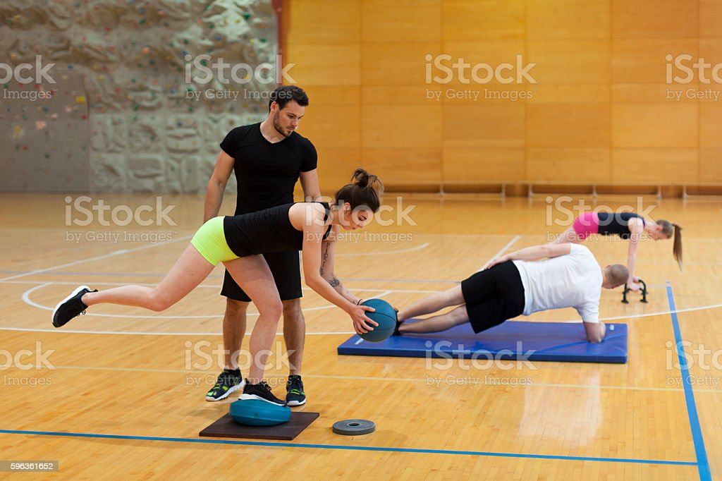 Fitness Teacher Helping Young Athletes do Exercises Wright in Gym royalty-free stock photo