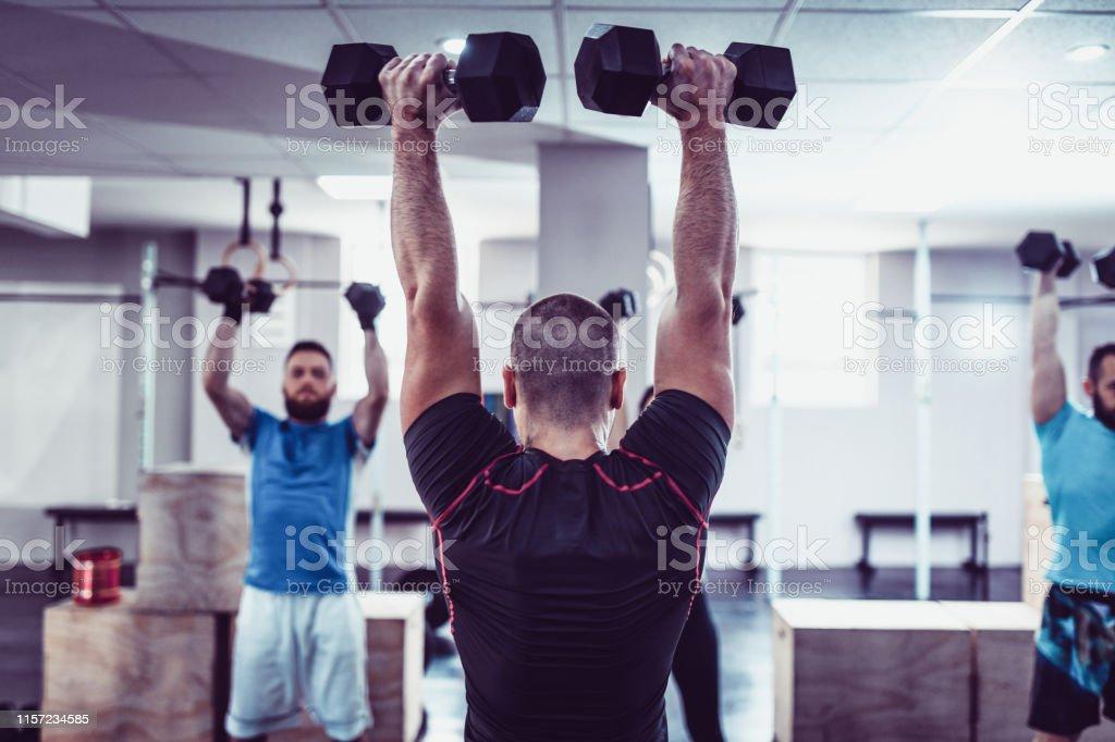 Fitness Team Doing Dumbbell Exercises In Gym