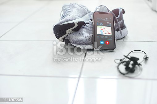 Mobile phone and headphones resting against a pair of trainers. The screen is displaying a fitness app showing the users run details.