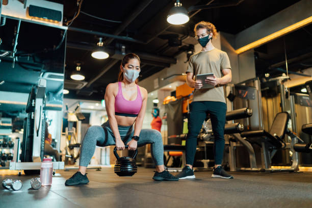 Fitness trainer checking condition of female athlete in gym while both of them wearing protective face masks for illness prevention stock photo