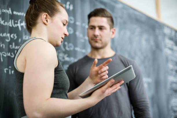 fitness-trainer trainingsplan mit client mit digital-tablette zu diskutieren - trainingsplan frauen stock-fotos und bilder