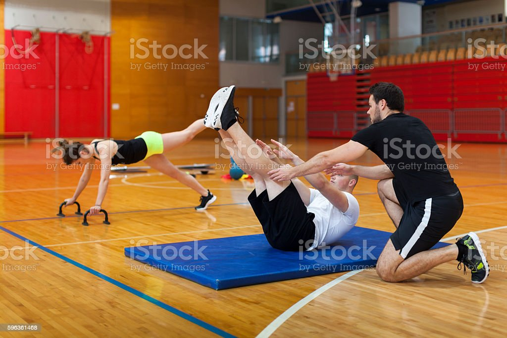 Fitness Trainer Helps With Exercises a Young Athlete in Gym royalty-free stock photo