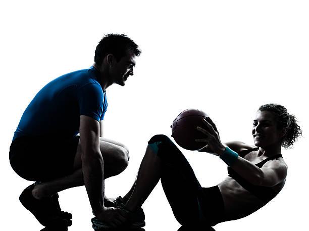 entrenador de ejercicios ayuda a las mujeres con pelota de ejercicio - entrenador personal fotografías e imágenes de stock