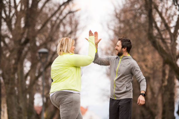 Fitness trainer in park taking high five with her client. stock photo
