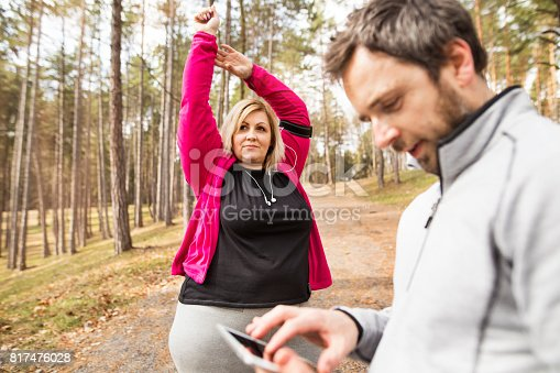 Fitness trainer outside in park tracking progress of his client - attractive overweight blonde woman running down the stairs