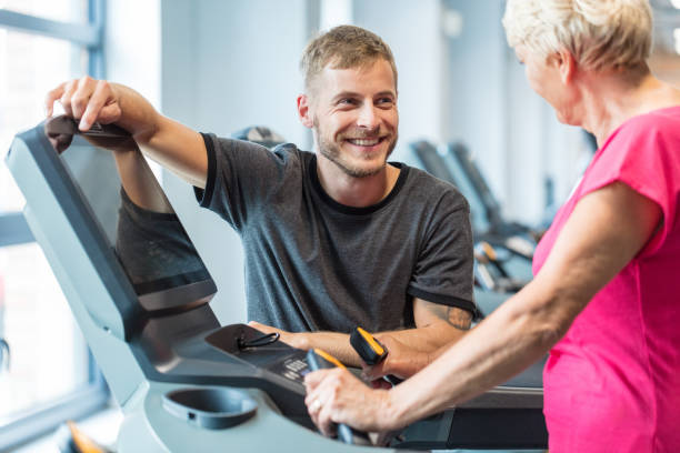 fitness trainer talking with senior woman exercising at rehab - runner rehab gym foto e immagini stock