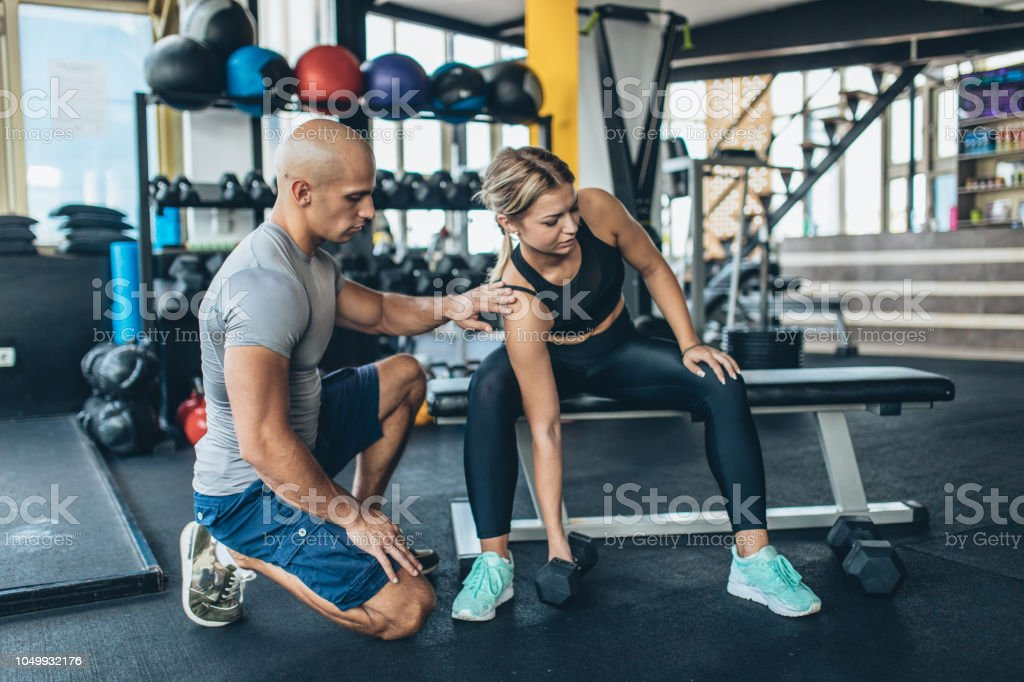 Two people, man fitness trainer and woman trainee in gym,...