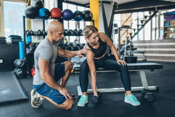 trainer fitness pesas de la chica de la enseñanza - entrenador personal fotografías e imágenes de stock