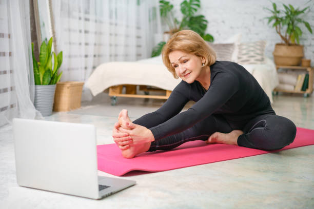 Fitness training online, senior woman at home with laptop stock photo