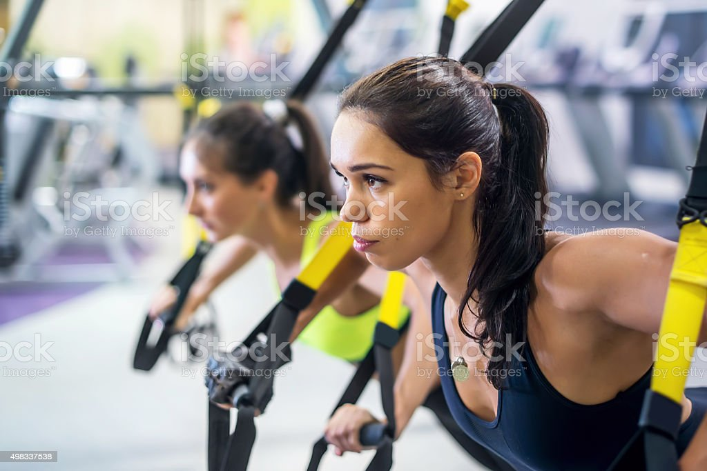 Fitness trx suspension straps training exercises women doing push-ups stock photo