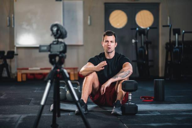 Fitness-Vlogger machen ein Video von sich im Fitnessstudio im Gespräch mit der Kamera – Foto