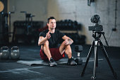 Fitness vlogger making a video of himself at the gym talking to the camera