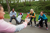 A group of mothers are doing a fitness bootcamp in the park with their babies in prams.