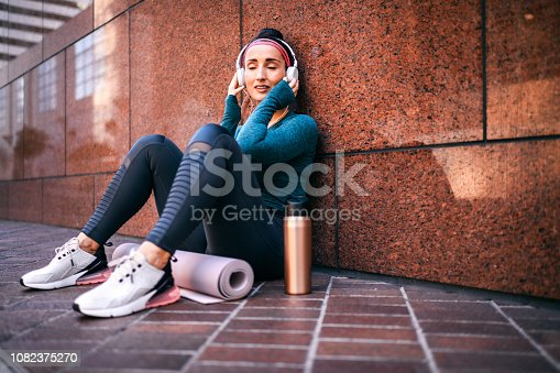 1091470492 istock photo Fitness woman carried away by music while sitting with her back against a marble building wall in a city street 1082375270