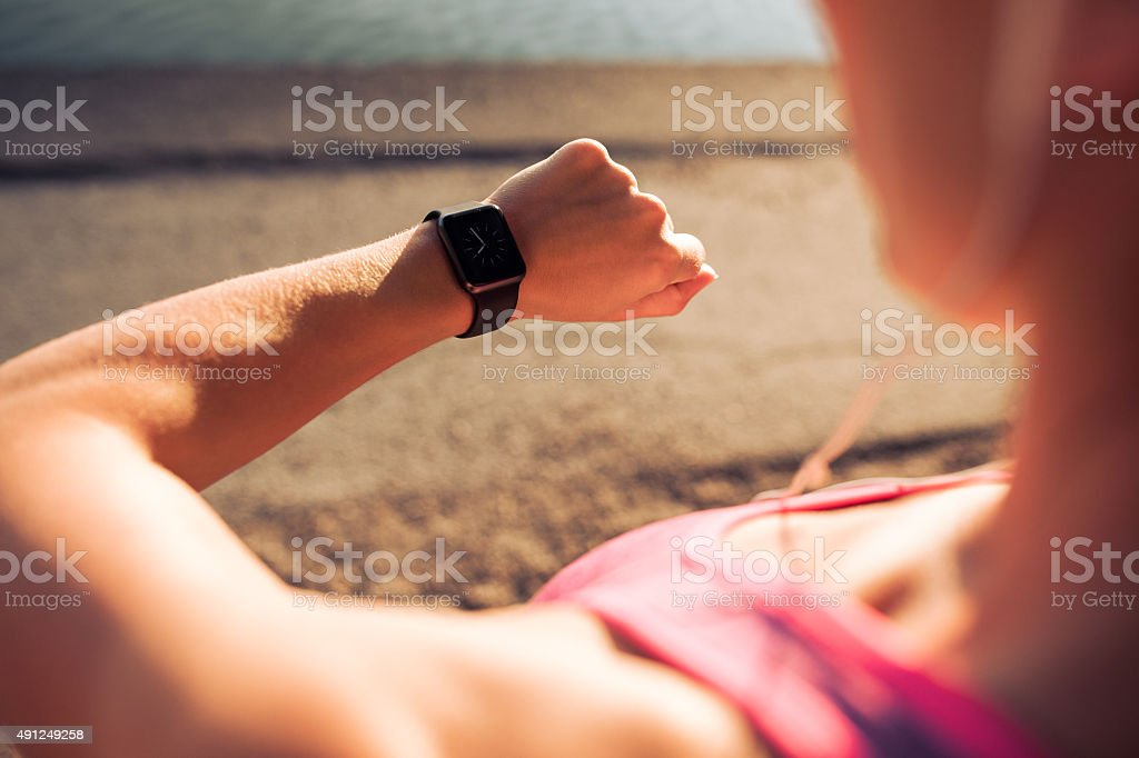 Fitness woman checking time on smartwatch stock photo