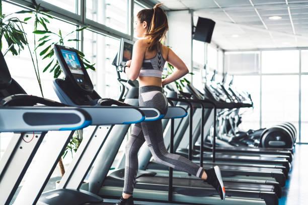 健身婦女在跑步機上做心肺療程 - 健身房 個照片及圖片檔
