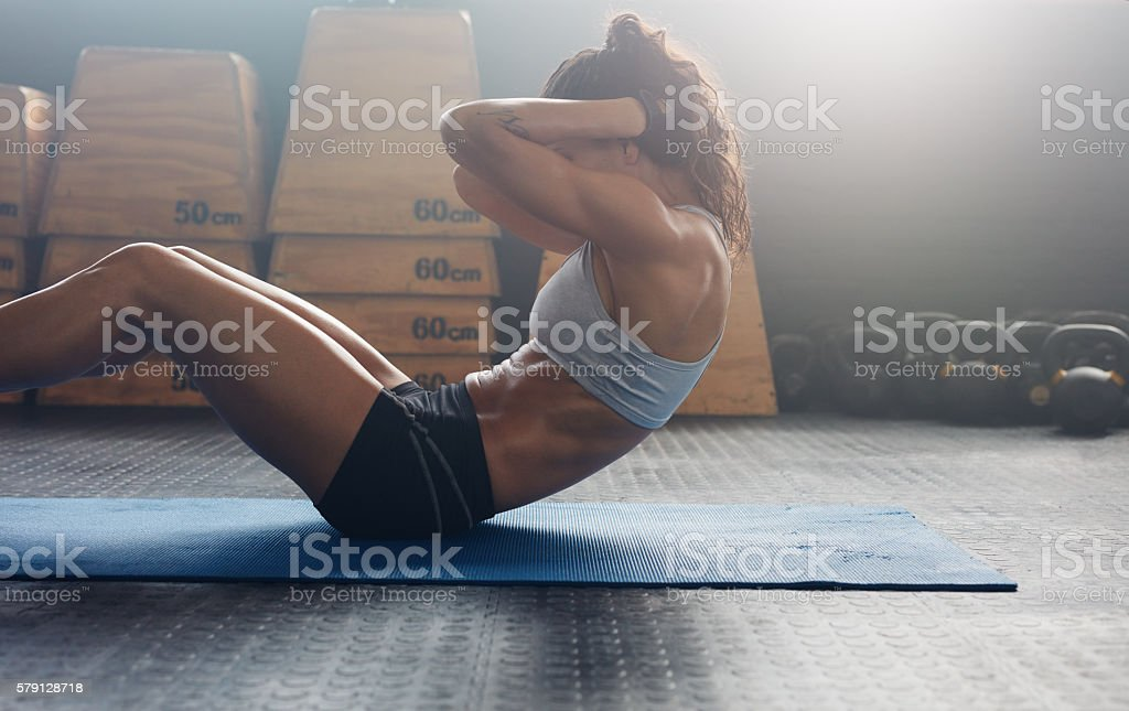 Fitness woman doing abs crunches stock photo