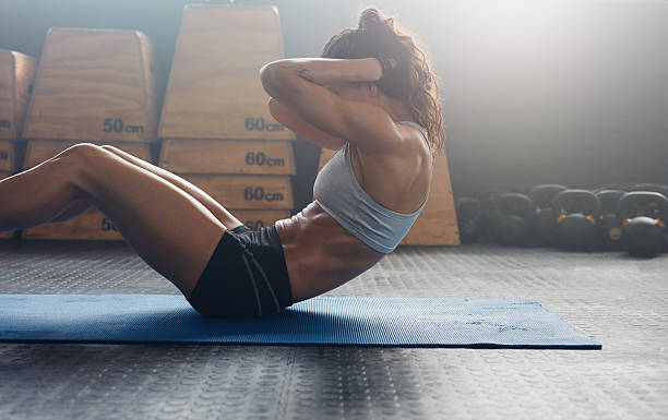 fitness woman doing abs crunches - human abdomen stock pictures, royalty-free photos & images