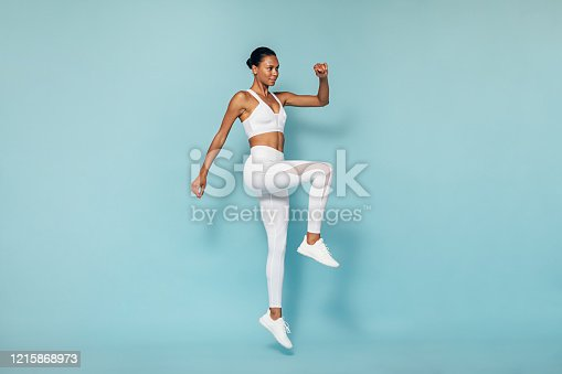 Fitness woman doing cardio training. Young female in sportswear jumping in studio.