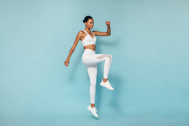 Fitness woman doing cardio training. Young female in sportswear jumping in studio. stock photo