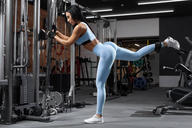Fitness woman doing exercise for glutes, cable kickbacks. Athletic girl workout at the gym. Beautiful butt in leggings stock photo