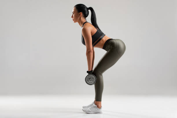 Fitness woman doing exercise for glutes on gray background. Athletic girl workout with dumbbells stock photo