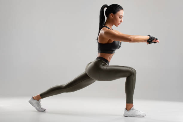 Fitness woman doing lunges exercises for leg muscle workout training. Active girl doing front forward one leg step lunge exercise stock photo