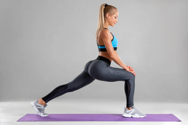 Fitness woman doing lunges exercises for leg muscle workout training. Active girl doing front forward one leg step lunge exercise, on the gray background stock photo