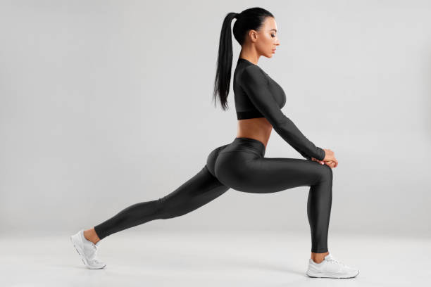 Fitness woman doing lunges exercises for leg muscle workout training. Active girl doing front forward one leg step lunge exercise for butt, isolated stock photo