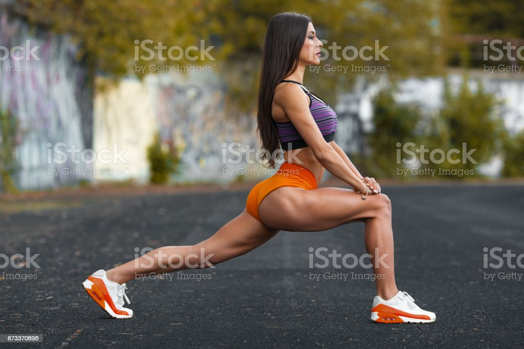 Fitness woman doing lunges exercises for leg muscle workout training, outdoors. Active girl doing front forward one leg step lunge exercise